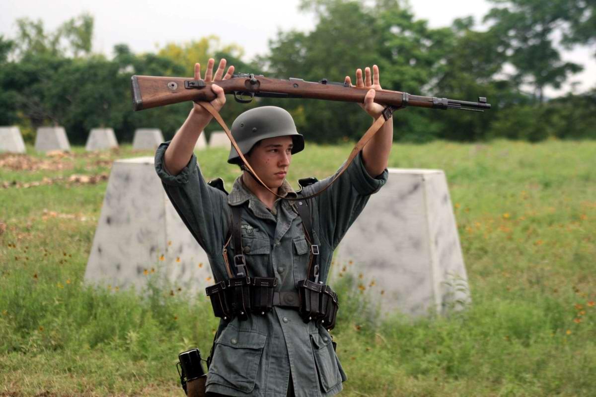 Молодой реконструктор из штата Техас в форме немецкого солдата разыгрывает сцену сдачи в плен