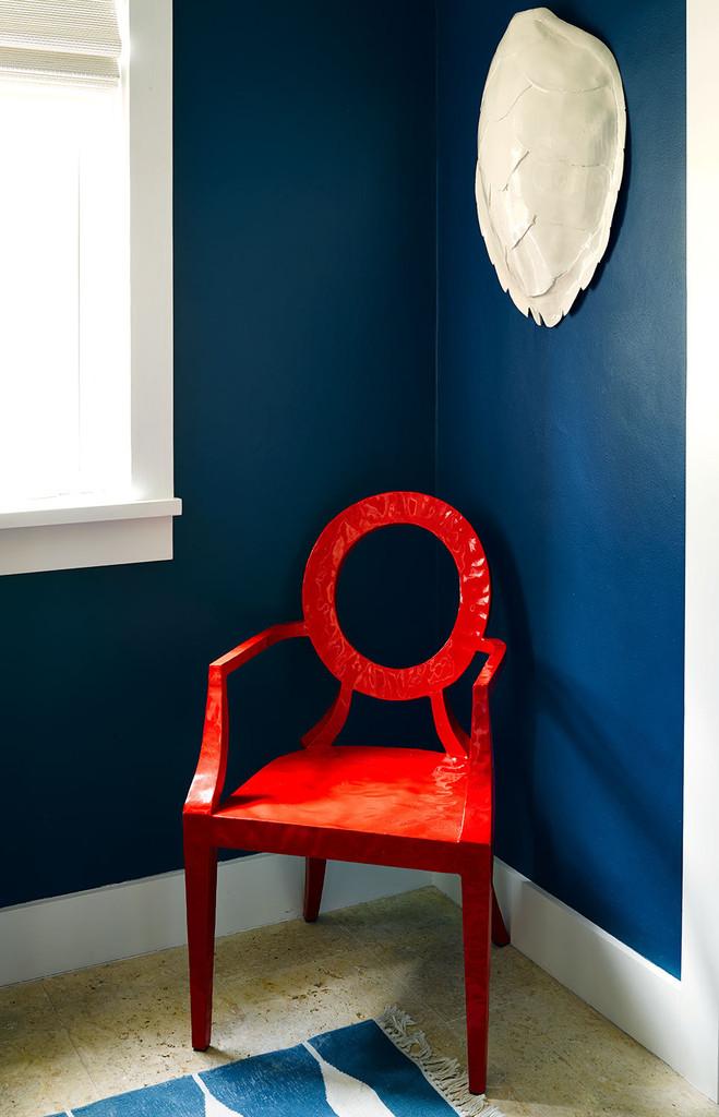 синяя стена, красное кресло
