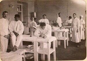 Медицинские сестры и братья милосердия делают перевязки раненым в процедурном кабинете госпиталя, оборудованного в здании Политехнического института.