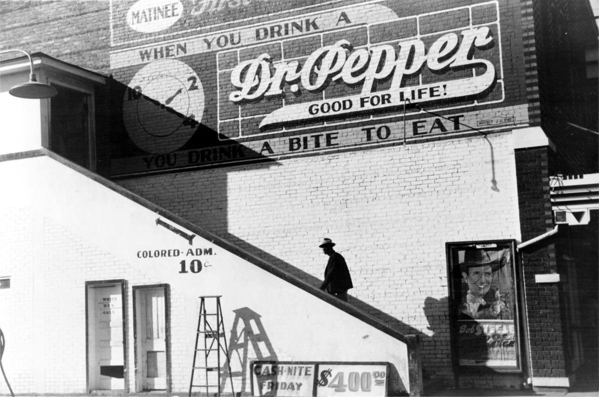 Кинотеатр. В левом нижнем углу дверь с надписью Только для белых, вверх по лестнице - Для цветных