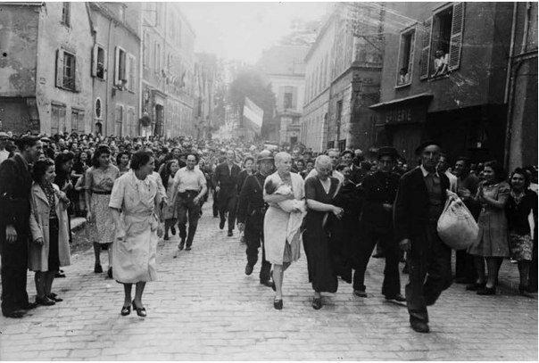 Роберт Капа. Толпа изгоняет из города обритых наголо женщину с ребенком, рожденным от немца, и ее мать. Шартр, 18 августа 1944.jpg