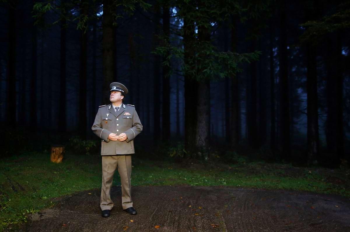 Экскурсовод, одетый в форму майора Национальной народной армии, ждёт очередную группу туристов у входа в бункер-музей