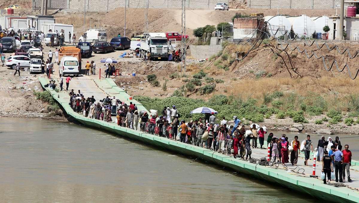 Беженцы переходят ирако-сирийскую границу по понтонному мосту через реку Тигр - вид с сирийского берега