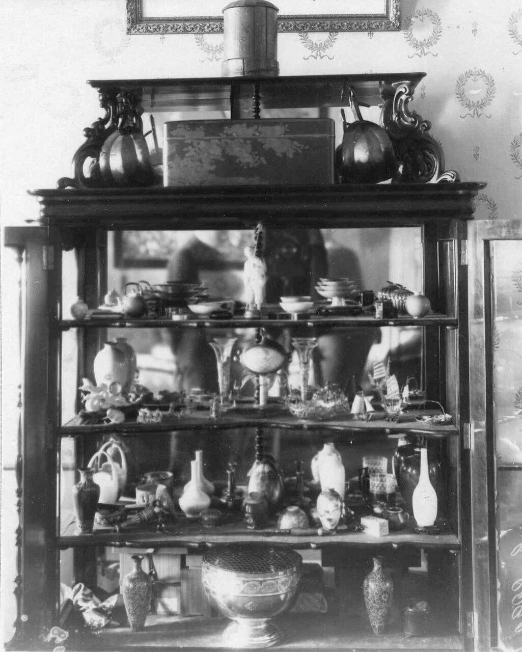 08. Шкафчик с коллекциями фарфоровой посуды и ваз, хрусталем в художественной оправе, ювелирными изделиями, поделками из лака и пр