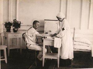 Медицинская сестра делает перевязку раненому.