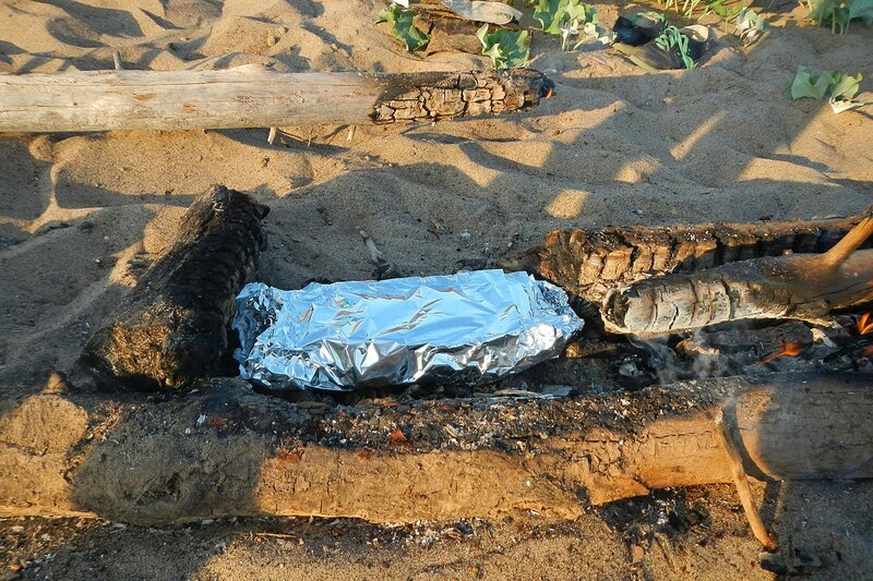 Рыба с овощами в фольге готовится на углях костра - походная еда
