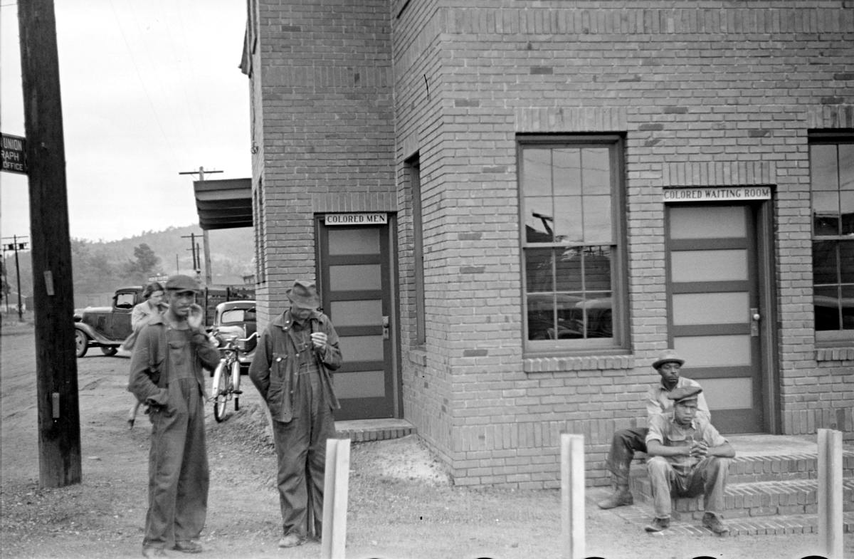 Афро-американцы у дверей автовокзала с надписями Вход для цветных и Комната ожидания для цветных