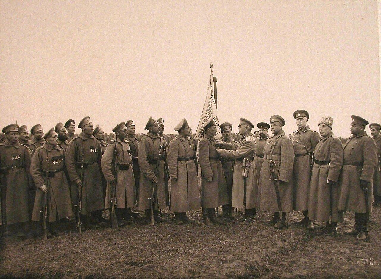20. Командир 34-го армейского корпуса генерал от кавалерии Цуриков(в центре) вручает нижним чинам Георгиевские кресты