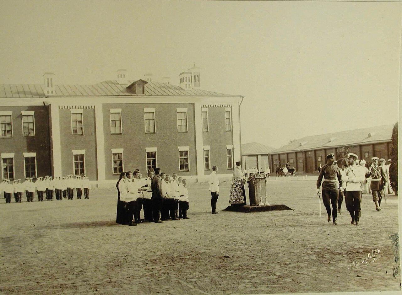 02.Император Николай II (справа) и сопровождающие его лица проходят по плацу во время молебна по случаю начала смотра артилерийских частей; в центре - священник и группа певчих