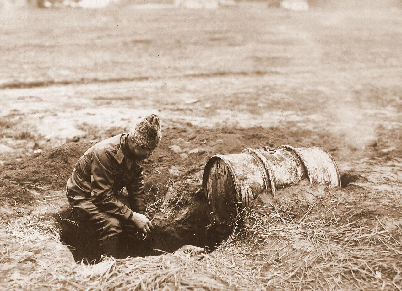 18. Один из членов авиационного отряда за разогреванием масла в земляной печи. 1915 Волынская губ., район г. Ровно