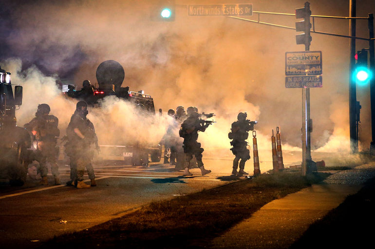 Police attempt to control demonstrators protesting the killing of teenager Michael Brown on August 18, 2014 in Ferguson, Missouri. Police shot smoke and tear gas to disperse the protestors with as they became unruly.  Brown was shot and killed by a Fergus