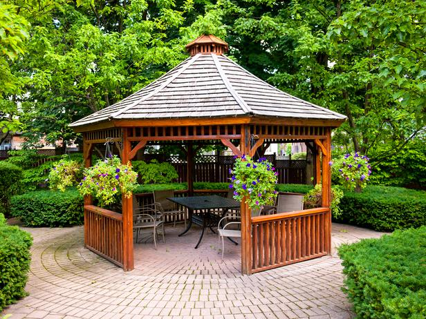 A paver patio with a beautiful wood gazebo situated in a garden.