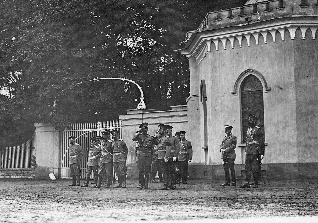 15. Император Николай II и сопровождающие его лица у ворот парка следят за проходящими мимо них автомобилями
