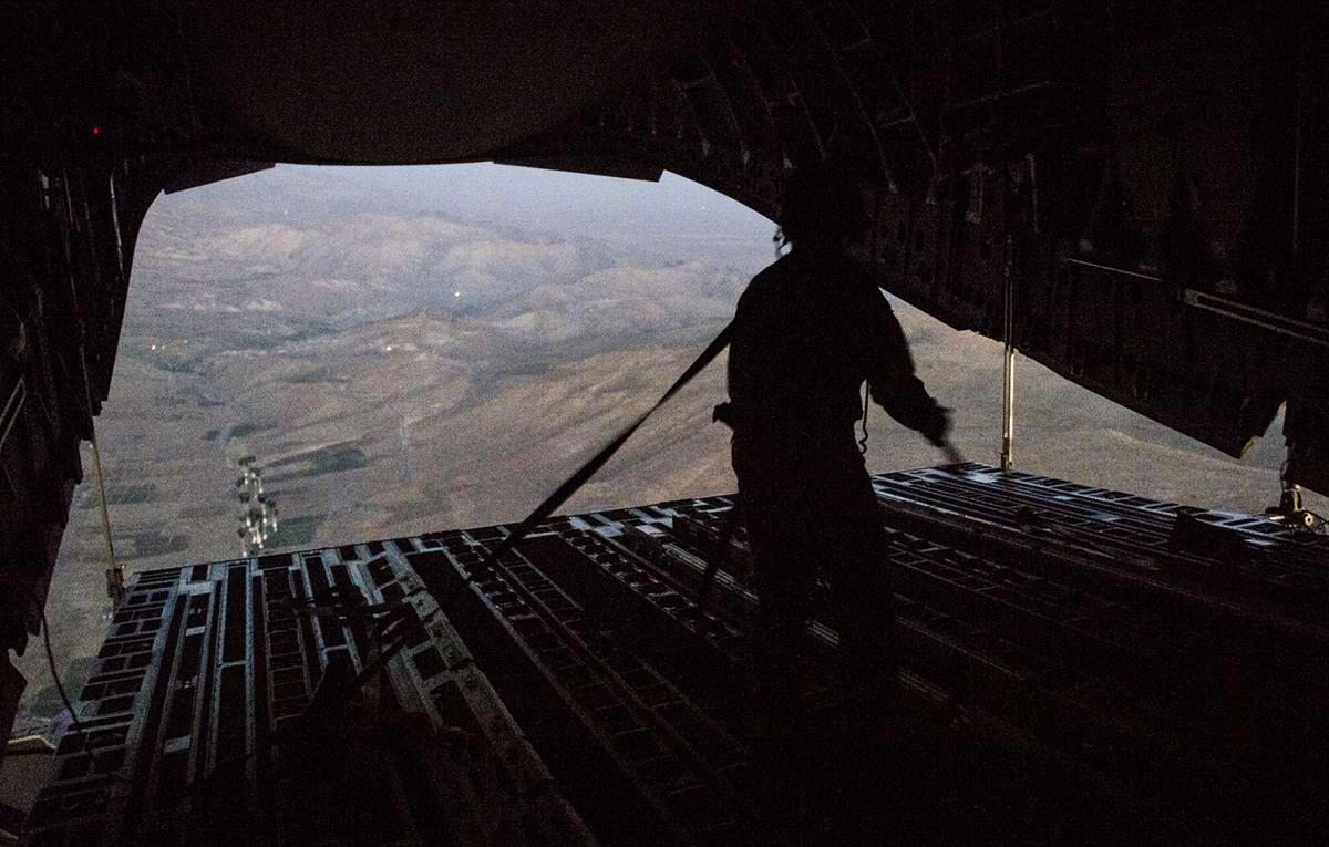 Процесс сброса поддонов с водой, продуктами и предметами первой необходимости с транспортного самолета ВВС США