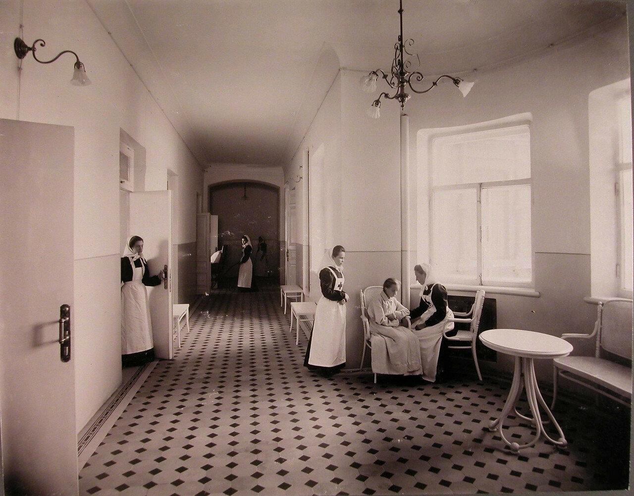 13. Сестры милосердия и пациентка в коридоре здания общины