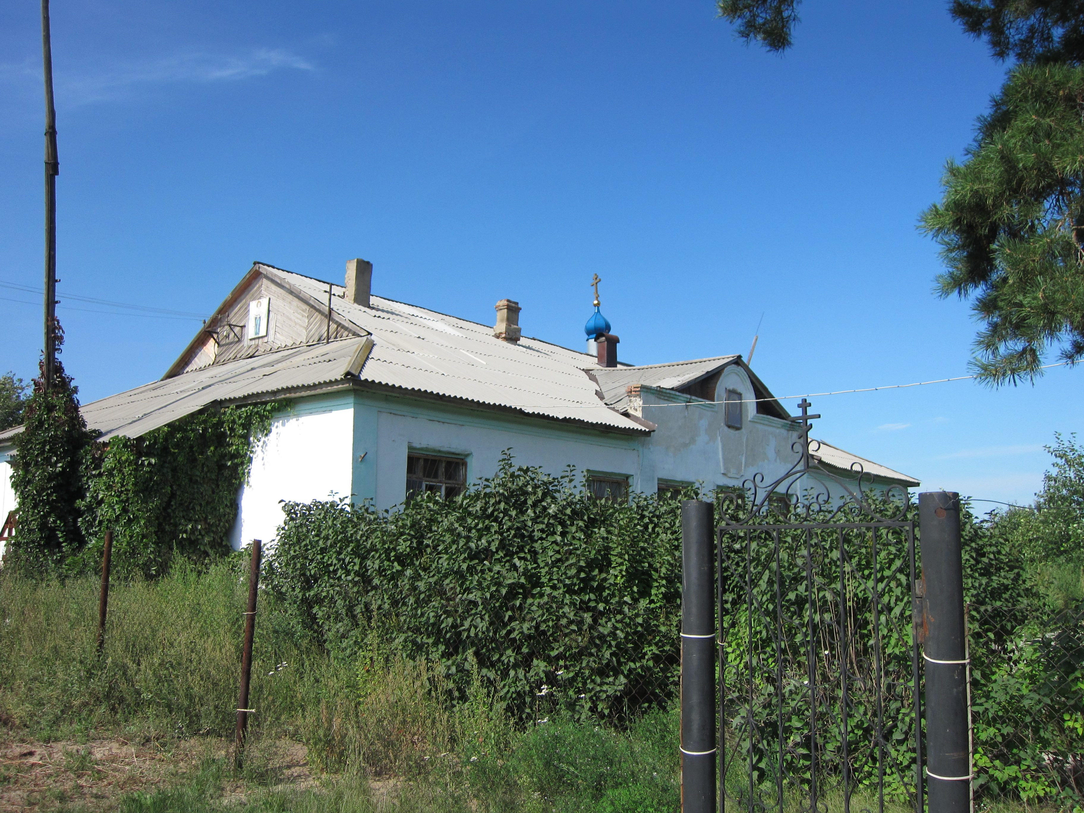 Неподалеку от новой церкви стоит старое здание, временно переоборудованное под храм (15.08.2014)