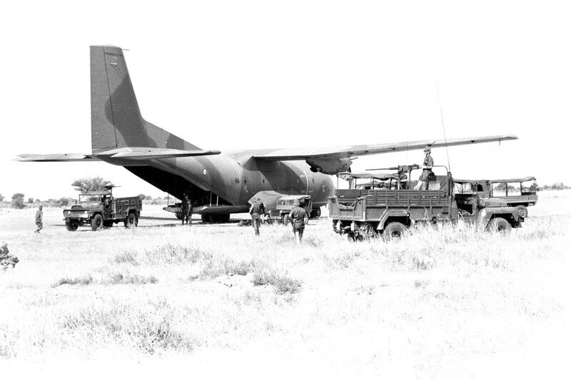 """Déchargement d'un avion Transall sur la piste d'Ati sous la protection d'une mitrailleuse de 12,7 mm, lors de l'opération """"Manta""""."""