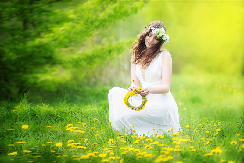 Image of pretty woman in a white dress weaves garland from dandelions in the field, happy  cheerful girl resting on dandelions meadow, relaxation outdoor in springtime, vacation.