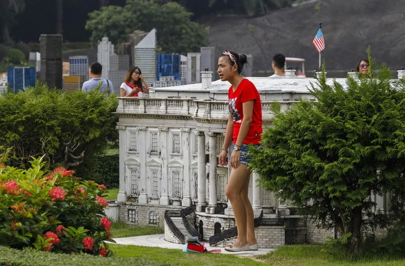 A woman stands next to a miniature replica of the U.S. White House at a theme park called