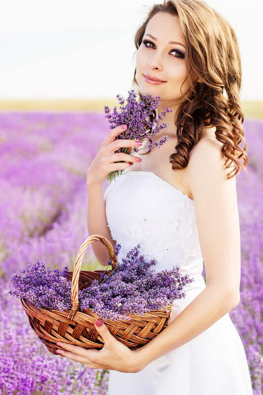 Beautiful bride posing at field of purple lavender with basket of flowers