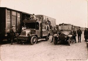 Группа солдат и офицеров (в автомобилях) у прибывшего на станцию эшелона с имуществом авиарот.