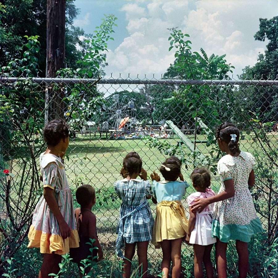 Негритянские дети толпятся и заглядывают через заграждение парка развлечений и отдыха Только для белых