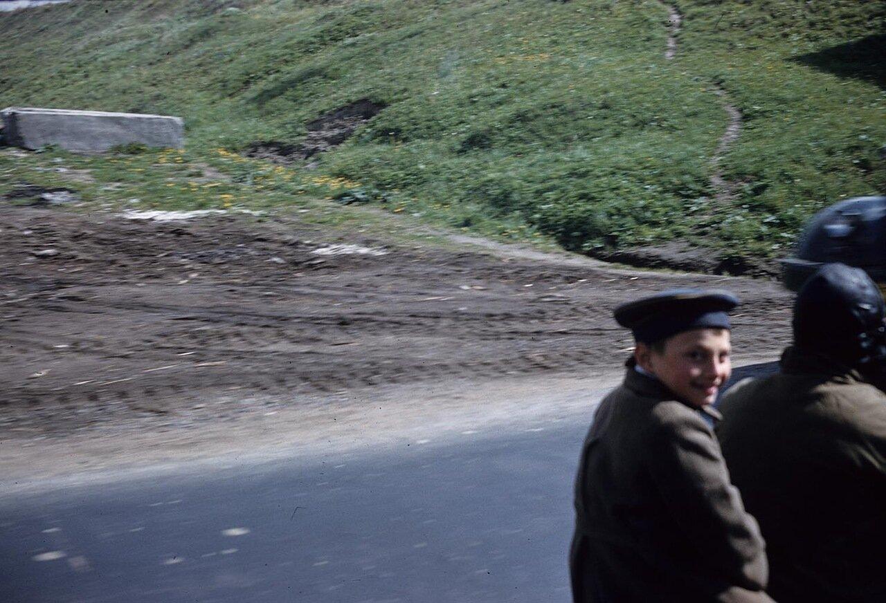 15. Мальчик улыбается в камеру на проселочной дороге