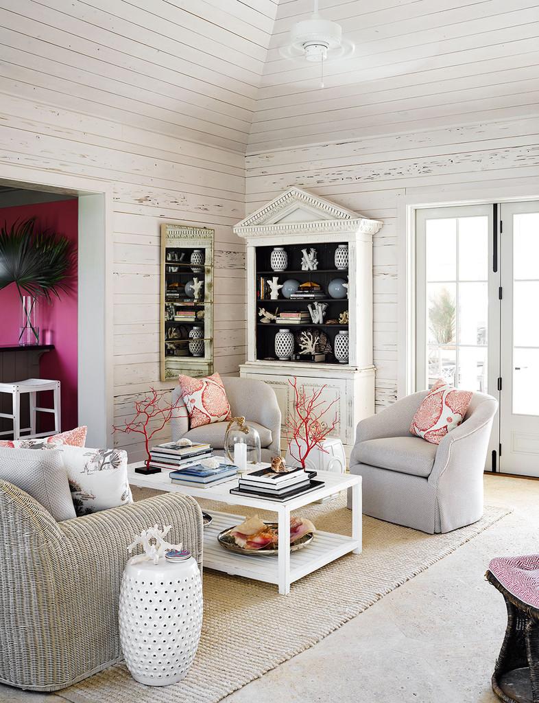 интерьер гостиной, кресла, стол. пуф, белый цвет, светлая мебель, красные акценты. дом на побережьи