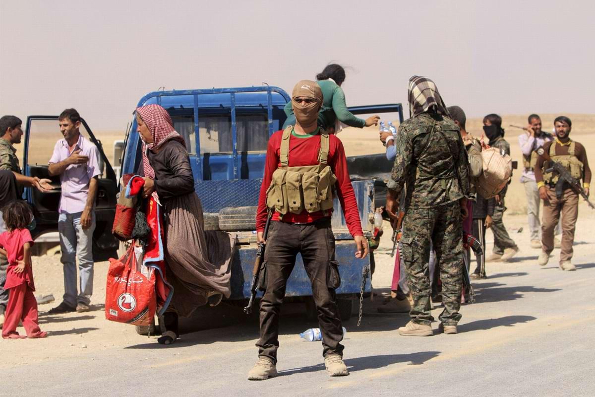 Бойцы курдских вооруженных формирований оказывают беженцам психологическую поддержку и раздают им воду (1)