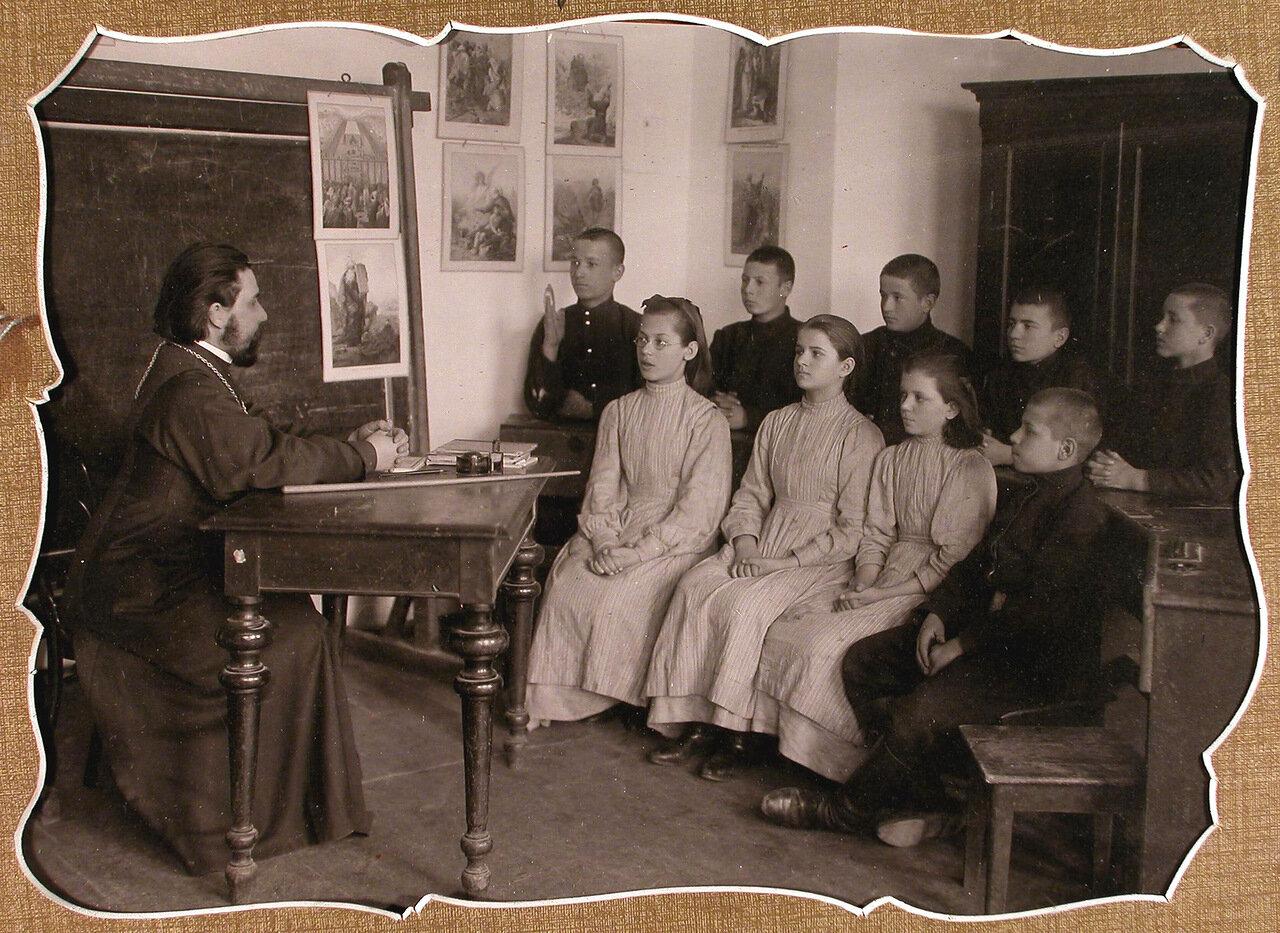 Группа учеников училища и законоучитель во время урока закона Божьего
