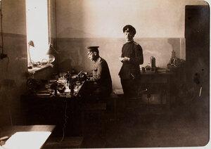Офицеры авиароты за работой в оптической мастерской.