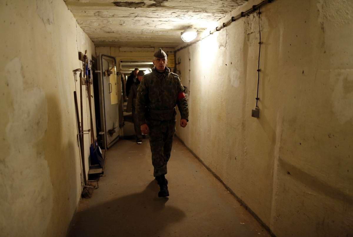 Один из работников музея проводит экскурсию по внутренним помещениям бункера