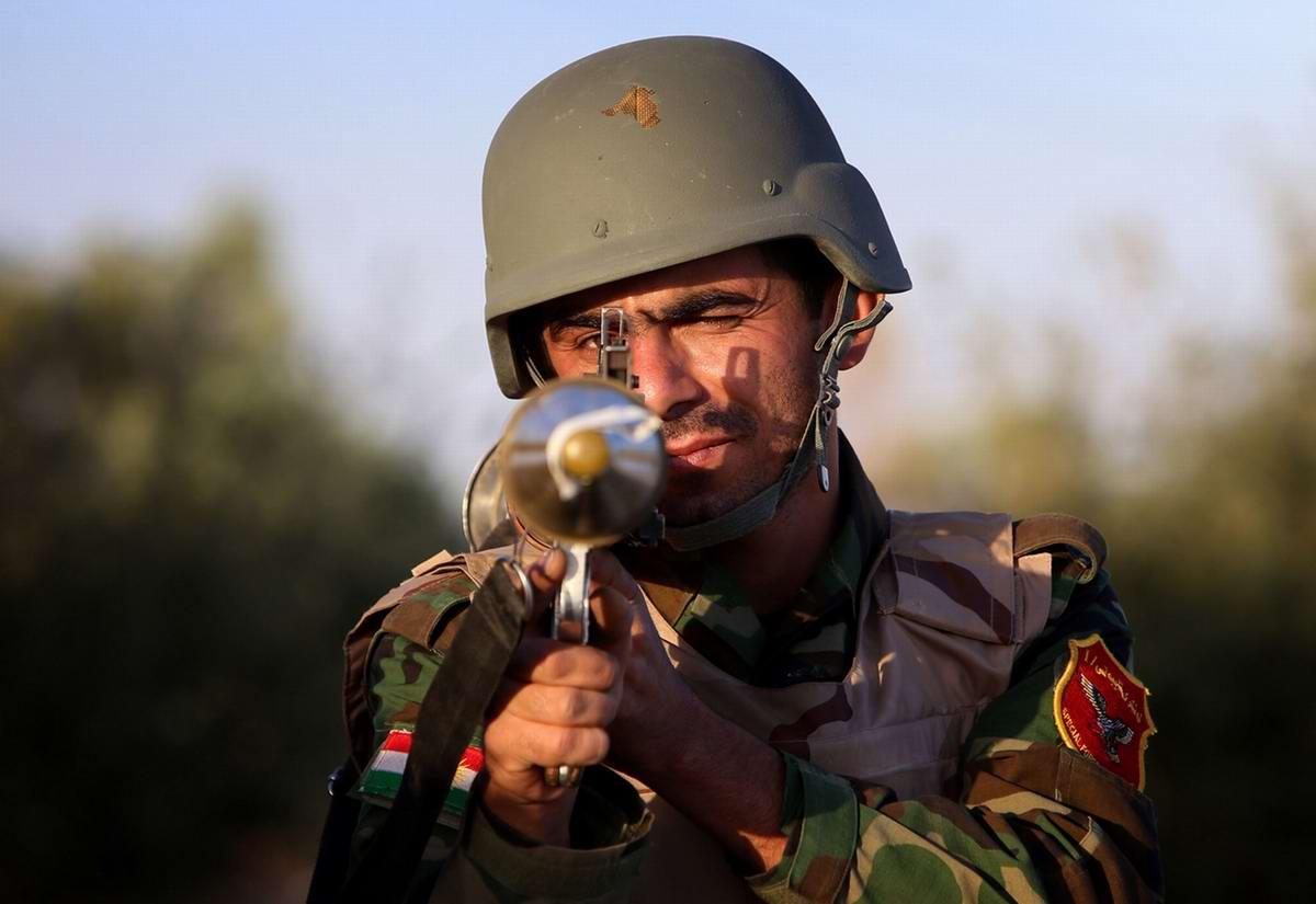 Боец военизированных формирований Иракского Курдистана с гранатометом в руках позирует фотографу на линии фронта в регионе Махмур (280 км к северу от Багдада)