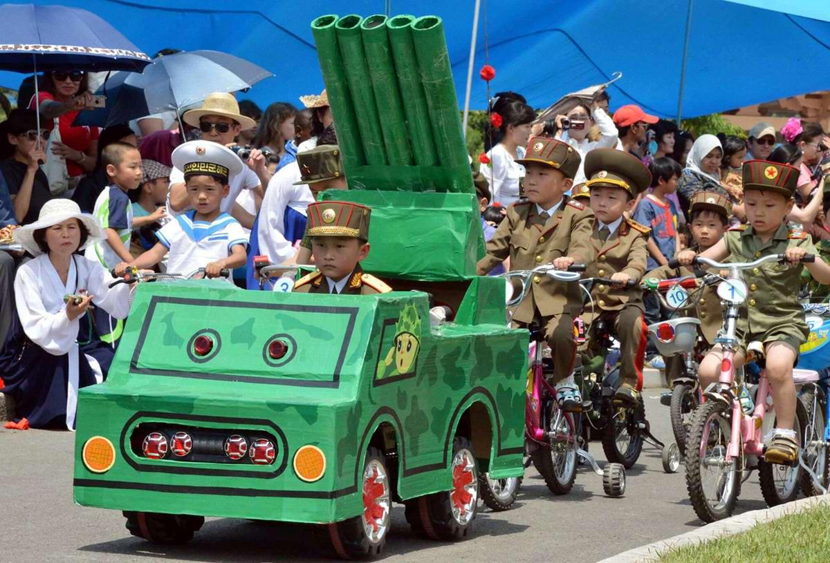 Северокорейские дети принимают участие в имитации военного парада в парке развлечений в Пхеньяне по случаю Дня защиты детей