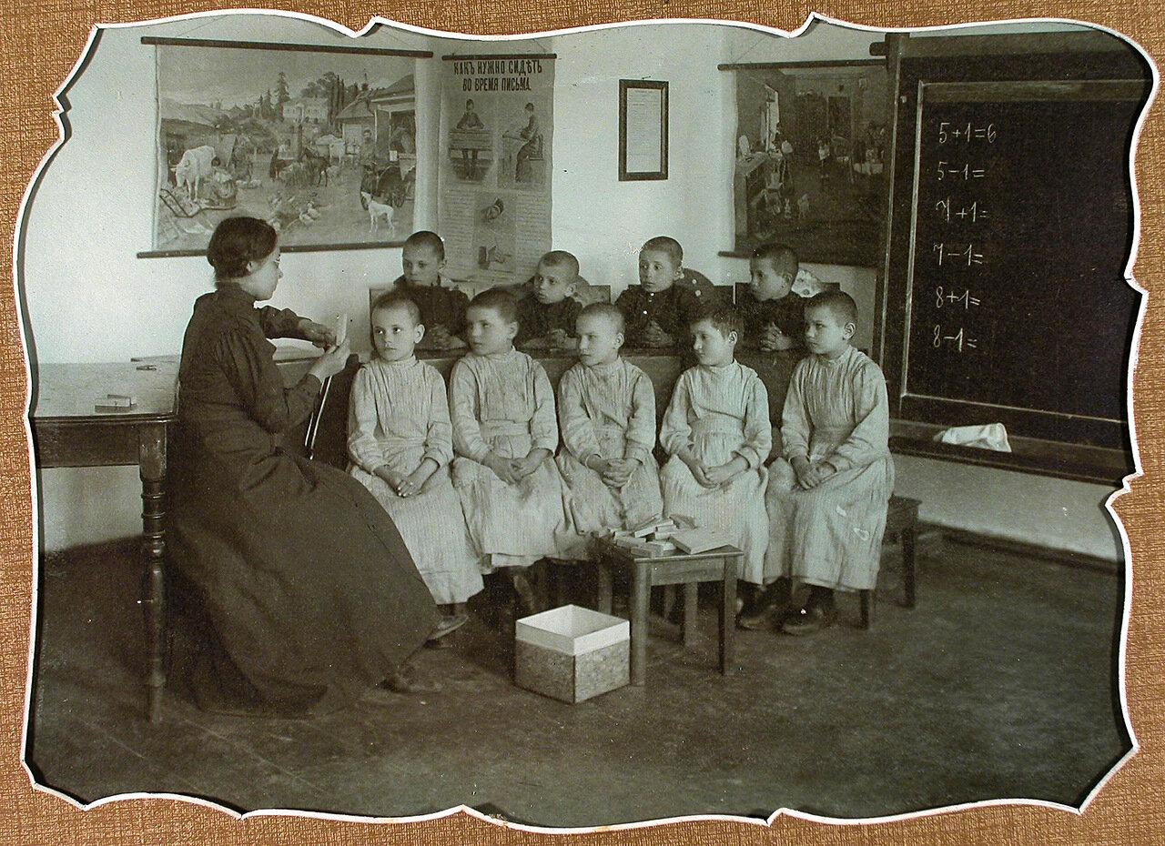 Учительница ведет урок арифметики с учениками 1-го года обучения