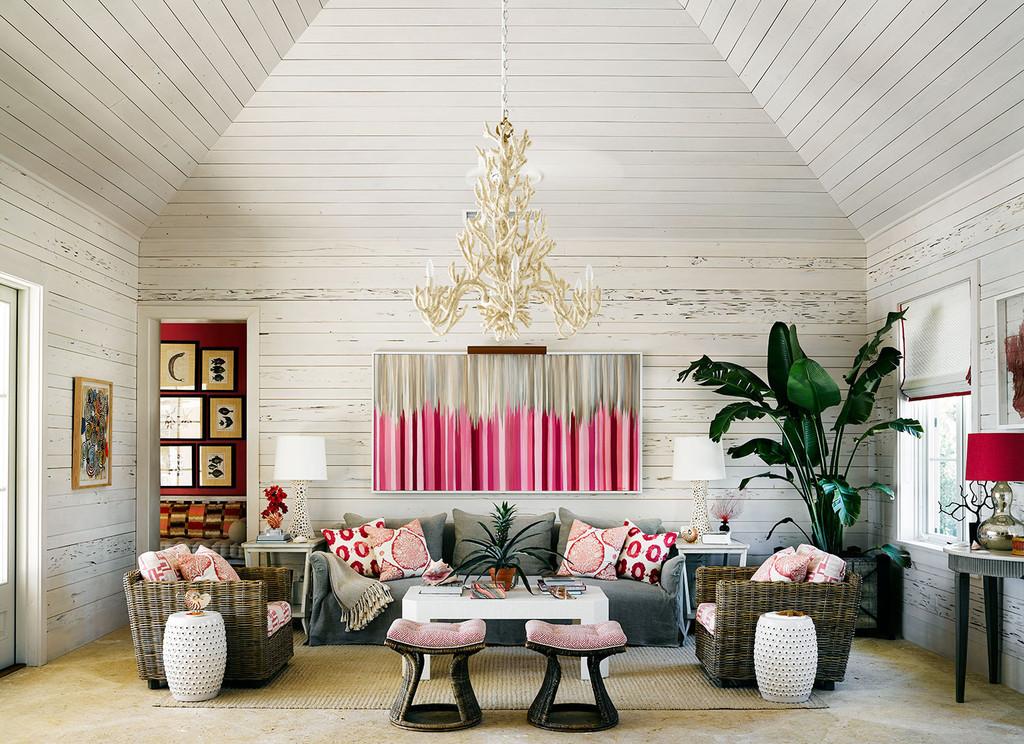 интерьер гостиной в доме на побережье, белые стены, акценты пурпурного цвета, диван, подушки, кресла, пуфы, пальма, люстра