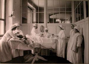 Врач и медицинские сестры перед началом операции в операционной лазарета, устроенного в Ермаковском ночлежном доме.