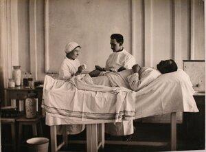 Врач и медицинская сестра делают перевязку раненому.