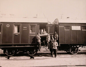 Группа санитаров поезда с носилками у специально оборудованной открытой для вноса тяжелораненых площадка.