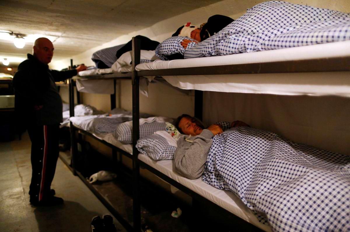 Гости укладываются на двухъярусные кровати для ночного сна в помещении казармы бункера-музея