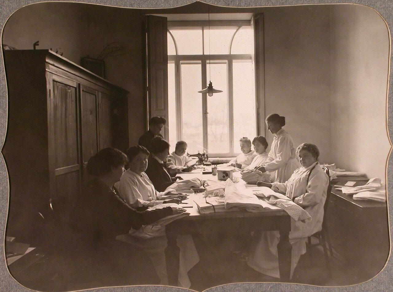 16. Сотрудницы Красного Креста готовят к выдаче в пошивочную, устроенную в одном из помещений общины, раскроенное белье