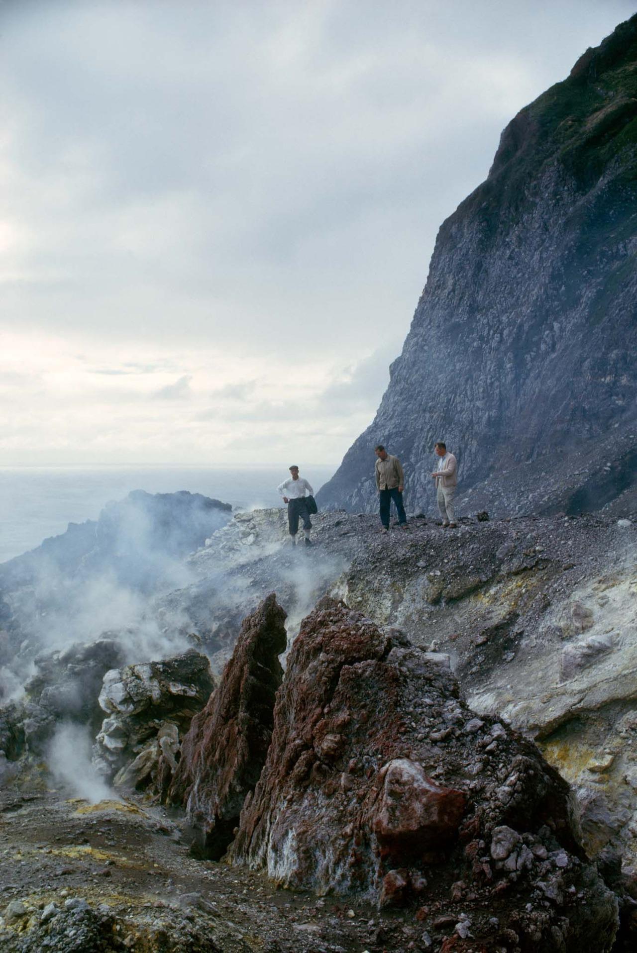 Men stand beside a volcano's crater eighteen months after an eruption on Tristan da Cunha Island, 1964.Photograph by James P. Blair