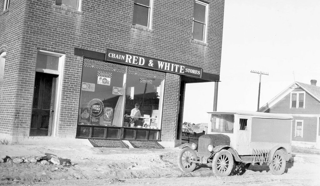"Brick storefront in Keota, Weld County, Colorado, has signs ""Chain Red & White Stores"", ""Lucky Strike Cigarette Groceries"" and ""Eat Ralston Health Growth for Boys and Girls"". 1928 Nov 5"