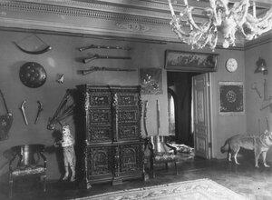 Часть кабинета со шкафиком резной работы и старинным оружием на стене.