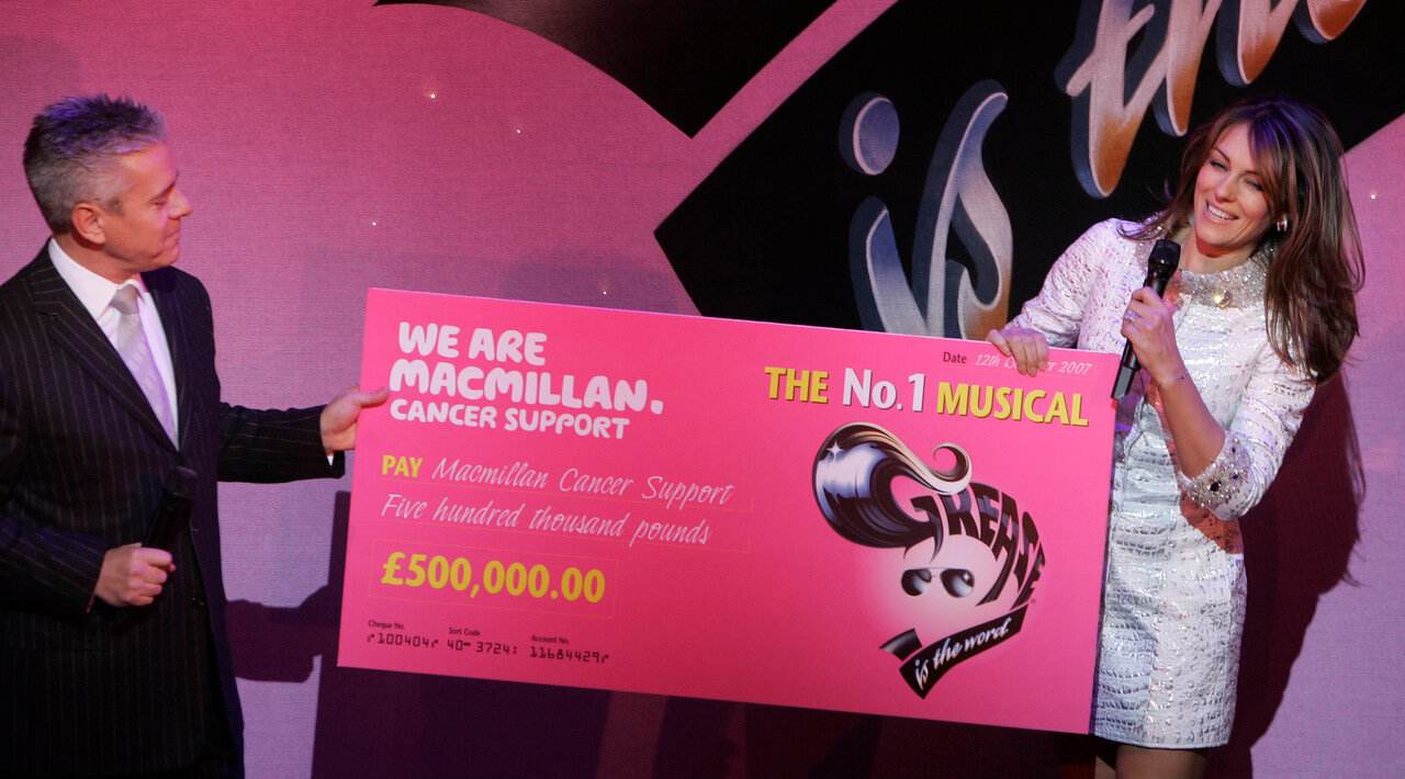British actress Elizabeth Hurley receives a cheque on behalf of Macmi