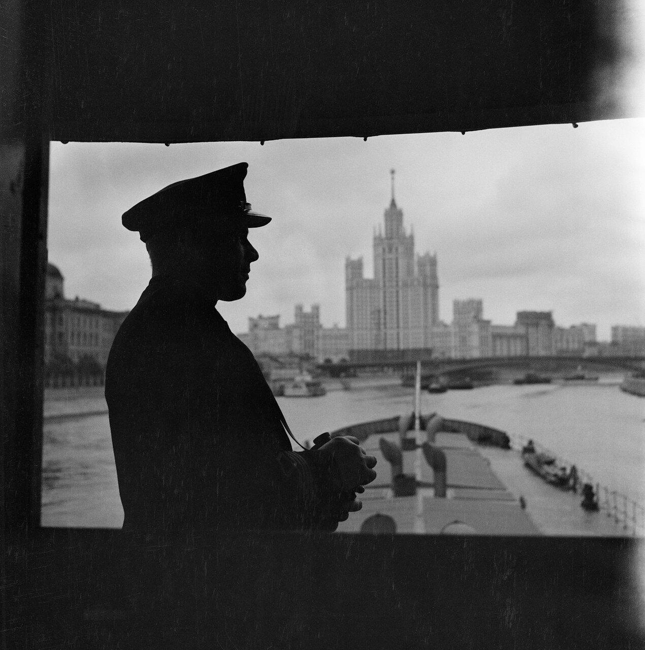 Капитан самоходного судна на фоне города
