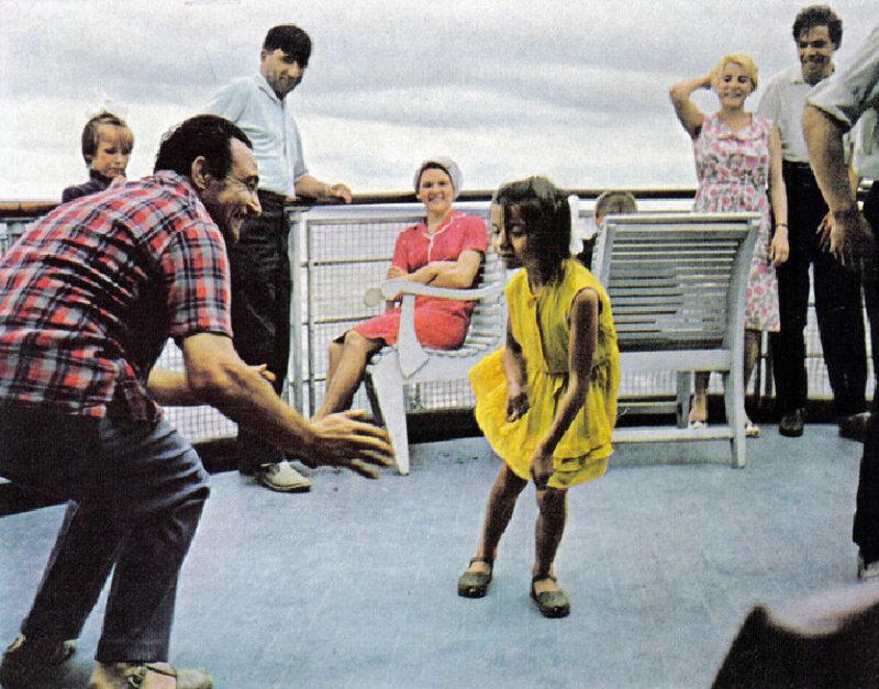На палубе теплохода один из гидов учит девочку танцевать твист