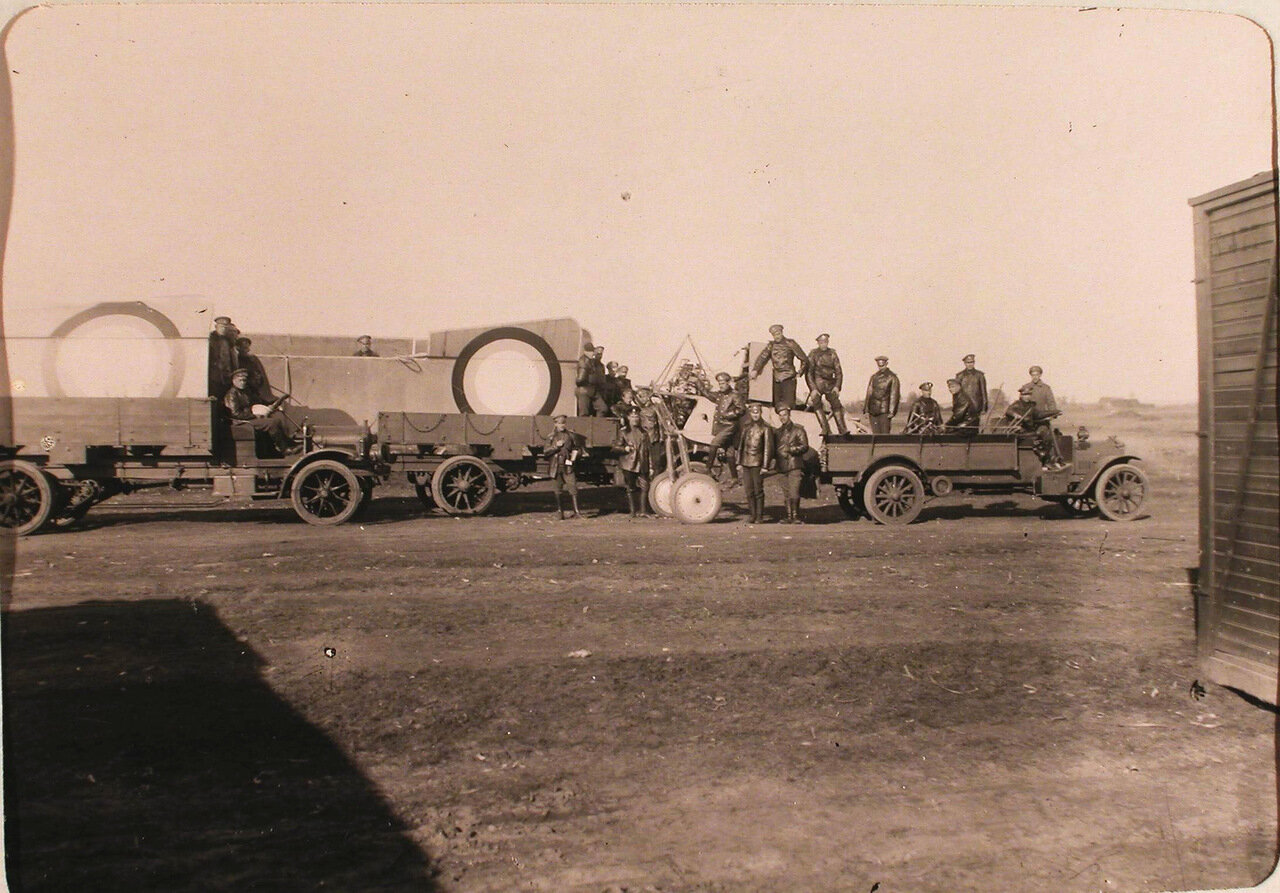 19.Группа механиков у автомобилей перед отправкой сломанного летательного аппарата поручика Гринева в мастерские роты