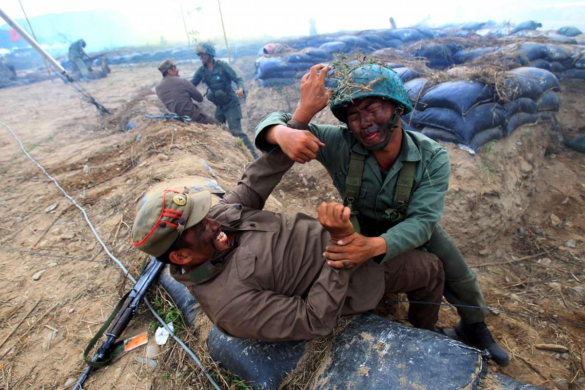 Сцены сражений между солдатами армий Северной и Южной Кореи времен военного конфликта начала 1950-х годов в исполнении переодетых солдат южнокорейской армии - 2