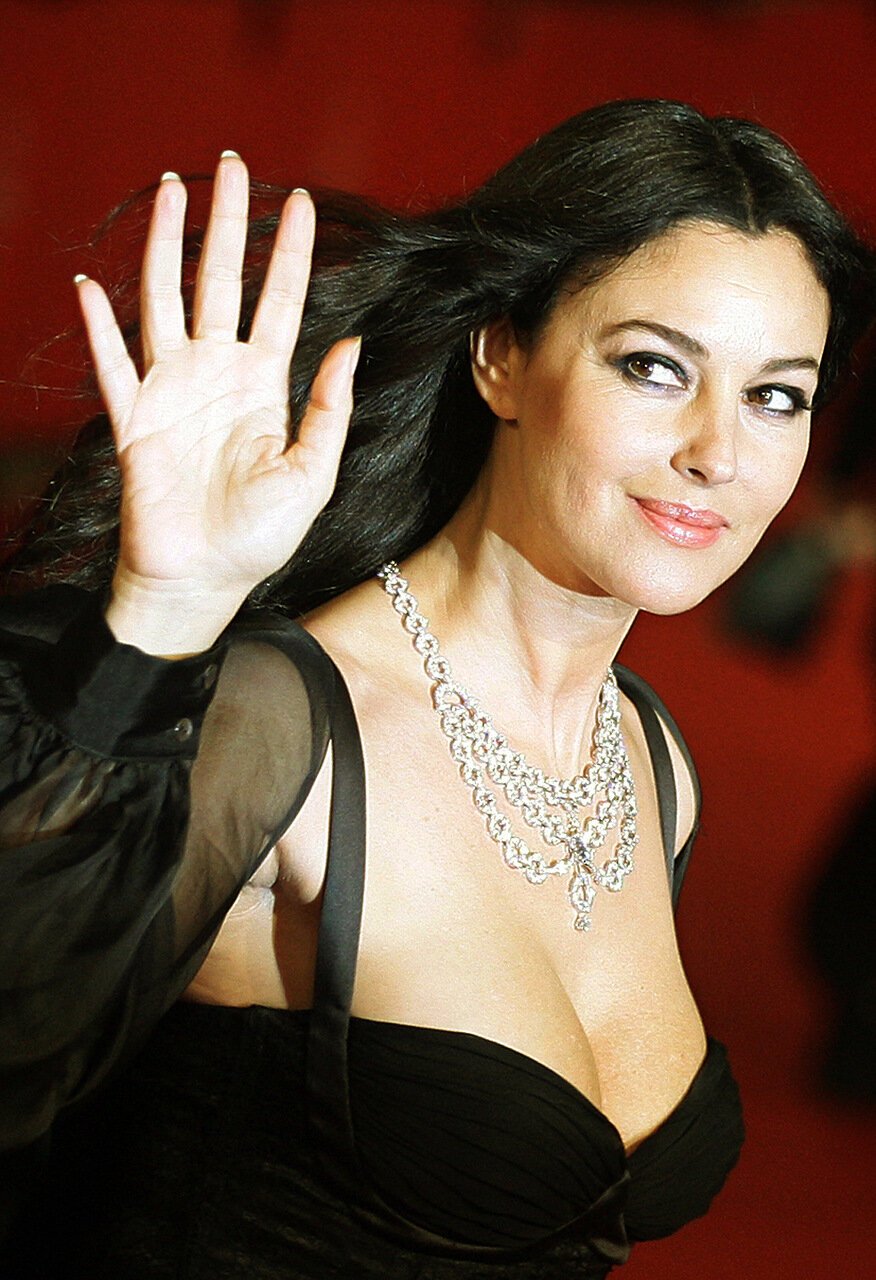 Italian actress Monica Bellucci waves to the photographers before the
